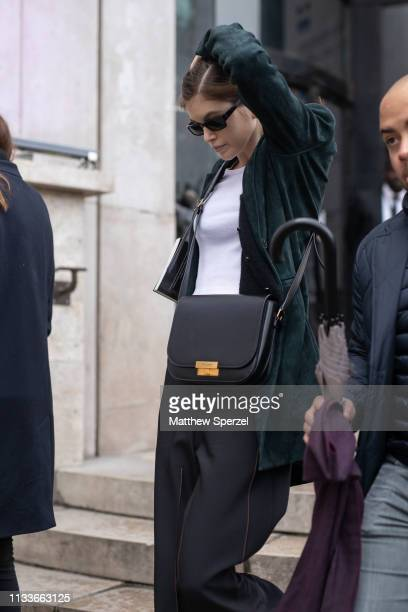 Kaia Gerber is seen on the street attending SACAI during Paris Fashion Week AW19 wearing dark green jacket and white shirt with black bag on March...