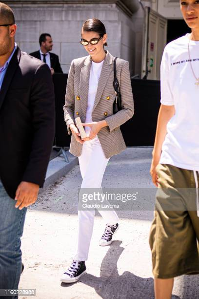 Kaia Gerber, wearing a white t-shirt, white jeans, checked blazer, black bag, Chanel sunglasses and black Converse, is seen outside Chanel show...