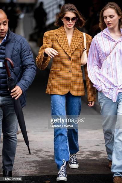 Kaia Gerber wearing an orange checked blazer and blue jeans is seen outside the Chanel show during Paris Fashion Week Womenswear Spring Summer 2020...
