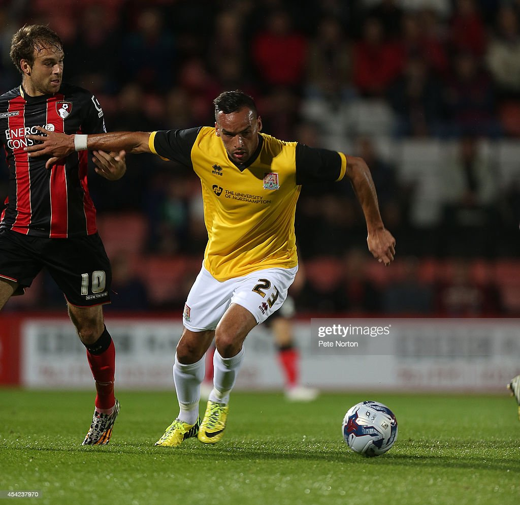 Kaid Mohamed of Northampton Town attempts to move away with the ball from Brett Pitman of AFC Bournemouth during the Capital One Cup Second Round match between AFC Bournemouth and Northampton Town at Goldsands Stadium on August 26, 2014 in Bournemouth, England.