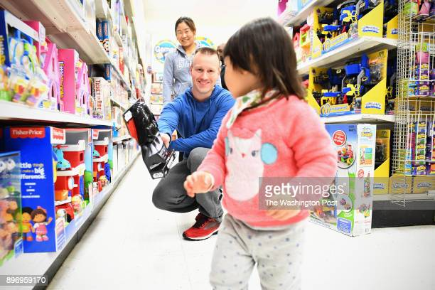 Kaighn Fosmoe 22months runs away as her father Kris Fosmoe shows her a Darth Vader toy while her mother June Fosmoe laughs at Toys R Us December 19...