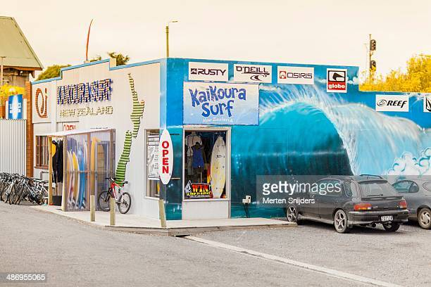 Kaikoura Surfshop showing a wallpainting of an aggressive barrel wave splashing down simply behind a regular parking lot