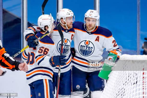 Kailer Yamamoto, Connor McDavid and Leon Draisaitl of the Edmonton Oilers celebrate a third period goal against the Winnipeg Jets at the Bell MTS...