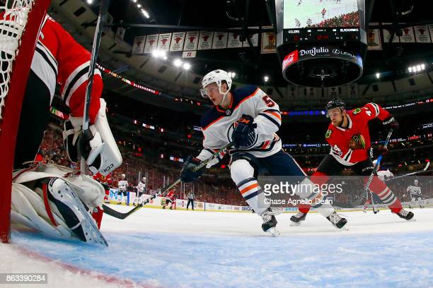 Kailer Yamamoto of the Edmonton Oilers and Jan Rutta of the Chicago Blackhawks skate at the United Center on October 19 2017 in Chicago Illinois The...