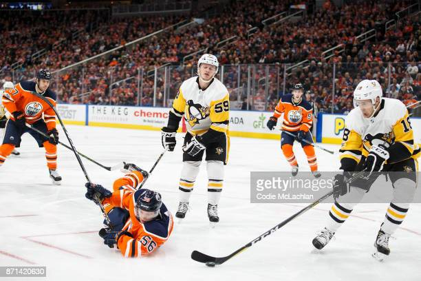 Kailer Yamamoto of the Edmonton Oilers draws a penalty against Jake Guentzel of the Pittsburgh Penguins at Rogers Place on November 1 2017 in...