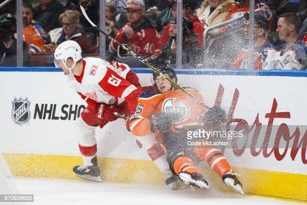 Kailer Yamamoto of the Edmonton Oilers is taken to the boards by Xavier Ouellet of the Detroit Red Wings at Rogers Place on November 5 2017 in...