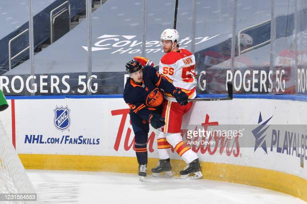 Kailer Yamamoto of the Edmonton Oilers lands a hit on Noah Hanifin of the Calgary Flames on March 6, 2021 at Rogers Place in Edmonton, Alberta,...