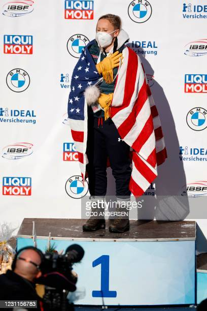 Kaillie Humphries is wrapped into her national flag as she celebrates on the podium after winning the women's monobob competition of the IBSF Bob and...