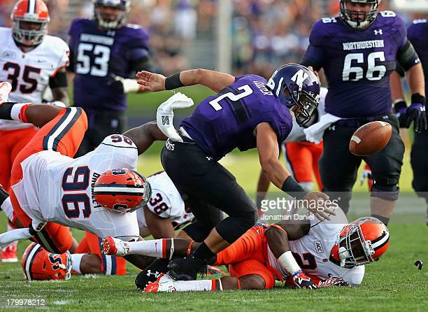 Kain Colter of the Northwestern Wildcats fumbles the ball as he is hit by Jay Bromley and Wayne Morgan of the Syracuse Orange at Ryan Field on...