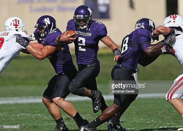 Kain Colter of the Northwestern Wildcats runs between blockers Dan Vitale and Demetrius Fields on his way to his fourth touchdown of the game against...