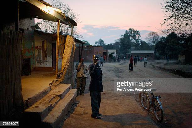 Kaipa Rabioni Mphandula age 48 smokes a cigarette outside a local bar on August 18 2006 in Mphandula village about 30 miles outside Lilongwe Malawi...