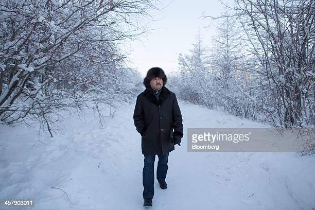 Kairat Zhakizhanov a Kazakh mine worker wears a sable fur hat as he walks along a frozen path past taiga forest in Udachny Sakha Republic Russia on...