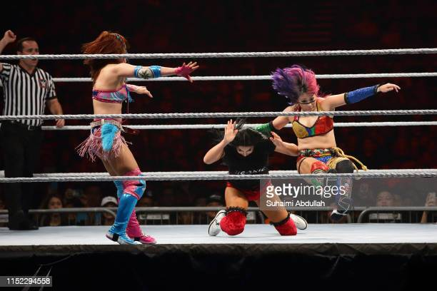 Kairi Sane and Asuka compete against Billie Kay of The IIconics during the WWE Live Singapore at the Singapore Indoor Stadium on June 27 2019 in...