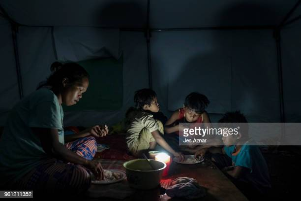 Kairon Ansayo and her children eat their last meal of the day before fasting for Ramadan inside their shelter at the Sarimanok tent city on May 15...