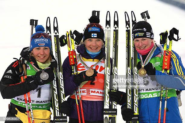 Kaisa Maekaeraeinen of Finland, Magdalena Neuner of Germany and Helena Ekholm of Sweden pose after the medal ceremony for the10km pursuit during the...