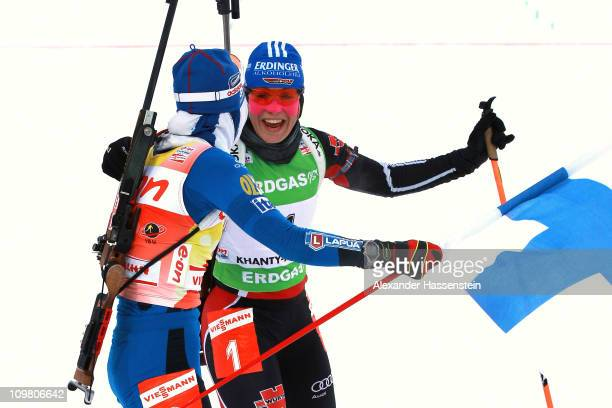 Kaisa Maekaeraeinen of Finland reacts at the finish area with Magdalena Neuner of Germany after winning the women's 10km pursuit during the IBU...