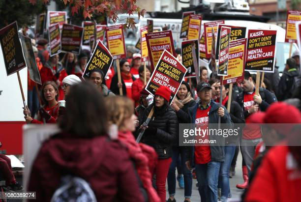 Kaiser Permanente mental health workers carry signs as they march in front of Kaiser Permanente San Francisco Medical Center on December 10 2018 in...