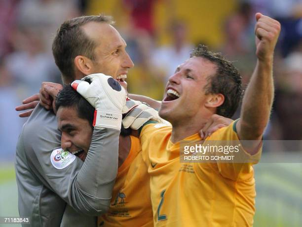 Kaiserslautern, GERMANY: Australian goalkeeper Mark Schwarzer , Australian midfielder Tim Cahill and Australian defender Lucas Neill celebrate their...