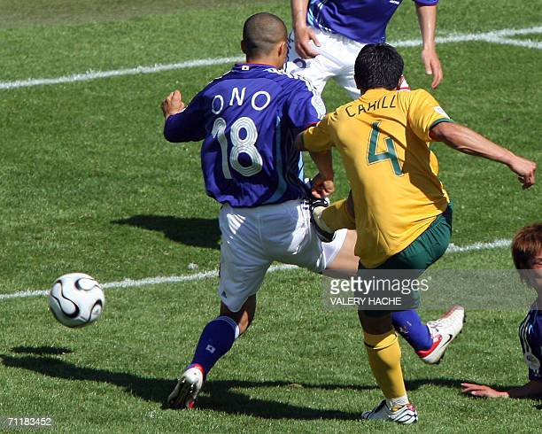 Australian midfielder Tim Cahill scores his second goal as Japanese midfielder Shinji Ono defends in their first round Group F World Cup football...