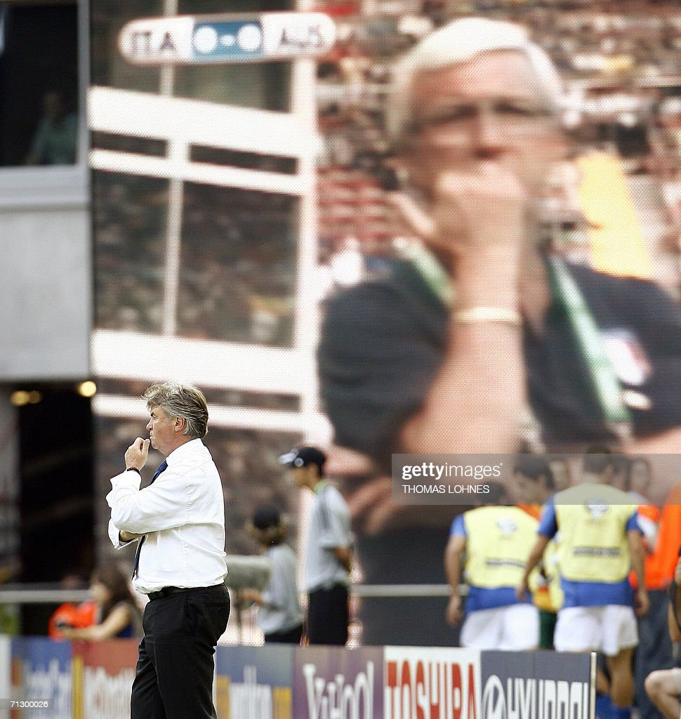 Dutch head coach of Australian team Guus Hiddink stands on the pitch while head coach of the Italian team Marcello Lippi appears on a giant screenin the background during the round of 16 World Cup football match between Italy and Australia at Kaiserslautern's Fritz-Walter Stadium, 26 June 2006. Italy won the match 1-0 when a penalty kick was converted by Italian midfielder Francesco Totti at the end of the game.