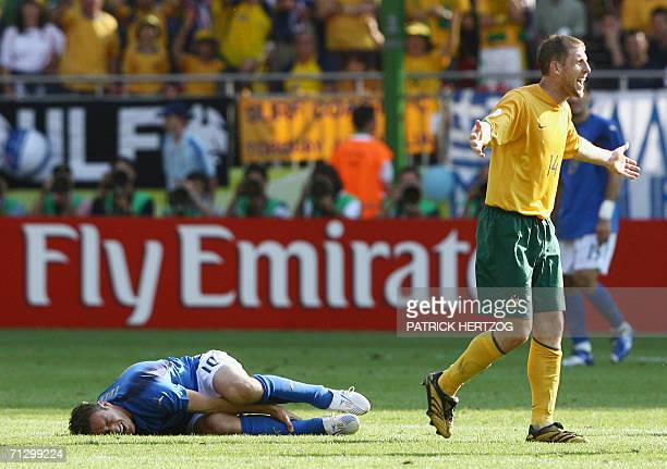 Italian midfielder Francesco Totti grimaces while holding his leg as Australian defender Scott Chipperfield protests during the round of 16 World Cup...
