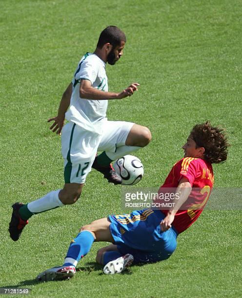 Saudi defender Abdulaziz Khathran is challenged by Spanish defender Michel Salgado during the opening round Group H World Cup football match between...