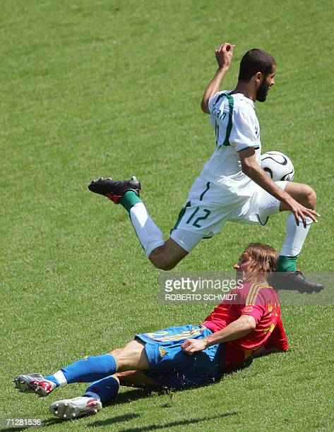 Saudi defender Abdulaziz Khathran jumps over a challenge by Spanish defender Michel Salgado during the opening round Group H World Cup football match...
