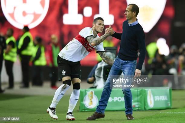 Kaiserslautern head coach Jeff strasser helping Stuttgart's Daniel Ginczek to get up from the floor during the DFBCup soccer match between 1 FC...