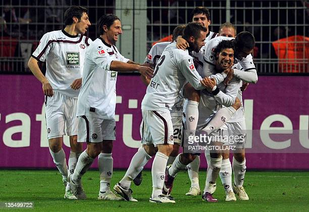Kaiserslautern's midfielder Olcay Sahan is congratulated by teammates after scoring during the German first division Bundesliga football match...