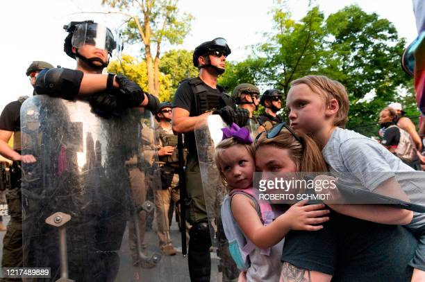 Kaitlin holds her threeyearold daughter Mikaela 3 and her son Jayce in front of a police barricade on a street leading to the front of the White...
