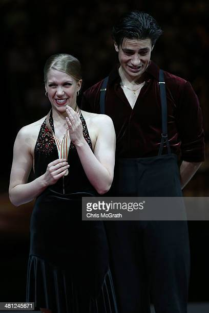 Kaitlyn Weaver and Andrew Poje of Canada react after being given the wrong medals during the victory ceremony for the Ice Dance Free Dance during ISU...