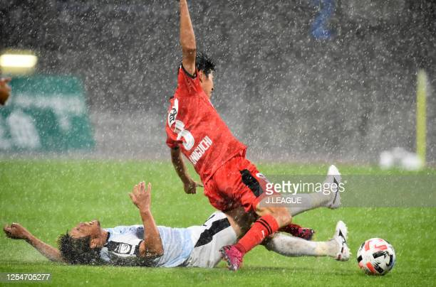 Kaito Taniguchi of Roasso Kumamoto is tackled by Kotaro Fujiwara of Kagoshima United during the JLeague Meiji Yasuda J3 match between Roasso Kumamoto...