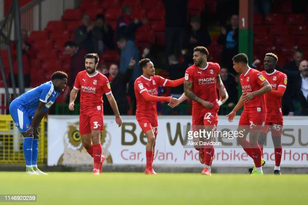 Kaiyne Woolery of Swindon Town celebrates with teammates after scoring his team's first goal during the Sky Bet League Two match between Swindon Town...