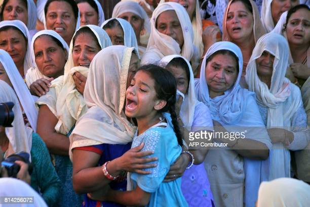TOPSHOT Kajal daughter of slain Indian soldier Lance Naik Ranjeet Singh wails as the mortal remains of her father are brought to her home in Burn...