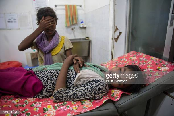 Kajal Nur is treated for injuries from a road traffic accident as her friend tries to comfort her at the 'Doctors Without Borders' Kutupalong clinic...