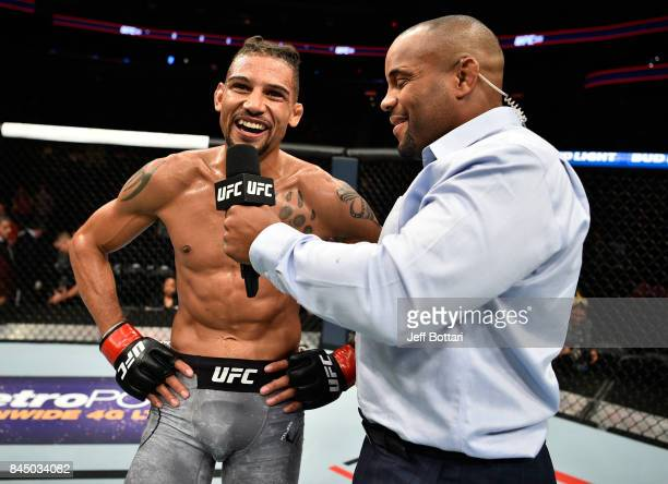 Kajan Johnson of Canada speaks to Daniel Cormier after his knockout victory over Adriano Martins of Brazil in their lightweight bout during the UFC...