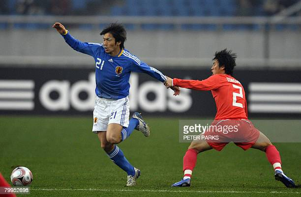 Kaji Akira of Japan is fouled by Lee Jong Min of South Korea in their final match in the East Asian Football Championships at the Olympic Sports...