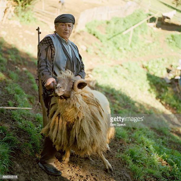 Kajtaz Lajci, aged 64, stands with her gun and her ram on her and her brothers' farm in Gjolaj. Being a sworn virgin gives her the otherwise...