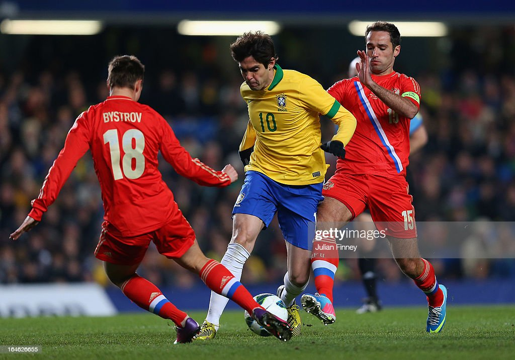 Kaka of Brazil goes past Bystrov Vladimir of Russia (L) and Shirokov Roman of Russia during the International Friendly match between Russia and Brazil at Stamford Bridge on March 25, 2013 in London, England.