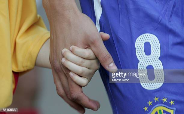Kaka of Brazil holds a hand of a child before the match between Mexico and Brazil in the FIFA Confederations Cup 2005 in the AWD Arena on June 19...