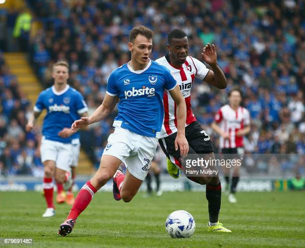 Kal Naismith of Portsmouth is chased down by Liam Davis of Cheltenham Town during the Sky Bet League Two match between Portsmouth and Cheltenham Town...