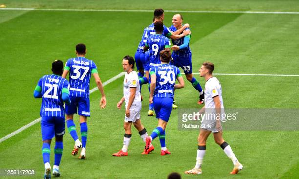 Kal Naismith of Wigan Athletic celebrates with his team mates after scoring his team's first goal during the Sky Bet Championship match between Wigan...