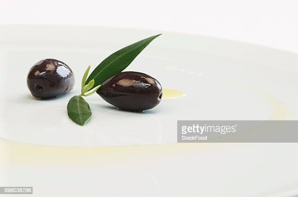 kalamata olives with leaves and olive oil on a plate - kalamata olive stock photos and pictures