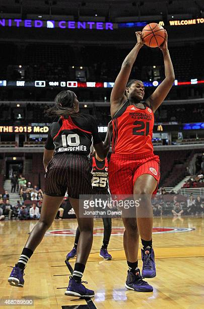 Kalani Brown of the West team rebounds over Beatrice Mompremier of the East team during the 2015 McDonalds's All American Game at the United Center...