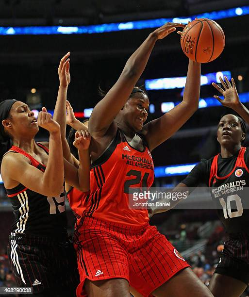Kalani Brown of the West team tries to rebound between Kiah Gillespie and Beatrice Mompremier of the East team during the 2015 McDonalds's All...