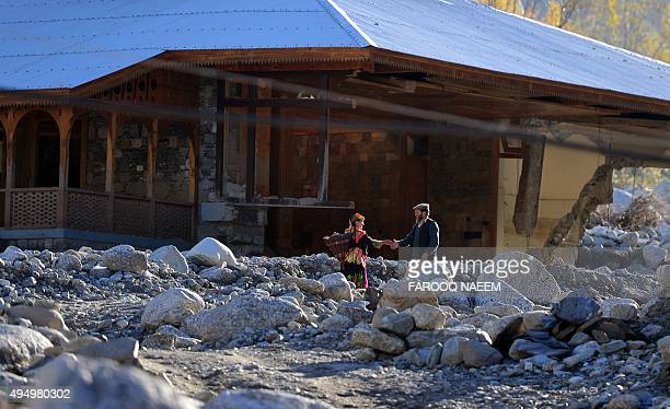 Kalash walk past a destroy hotel in a stream in Bumburate village of Kalash valley on October 30 2015 Kalash considered as the only surviving animist...