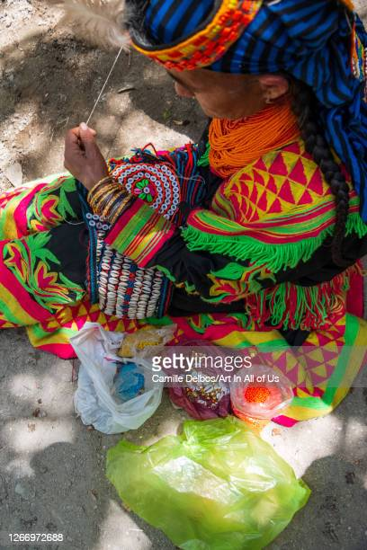 Kalash woman is embroidering a kupasik, the colorful headdress worn for celebration. It is mostly ornamented with mother-of-pearl buttons, shells,...