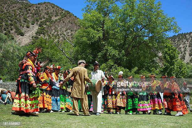 Kalash women and men dance and sing their way from the dancing ground to the village arena, the Charso, for the end of the day's festivities. Joshi...