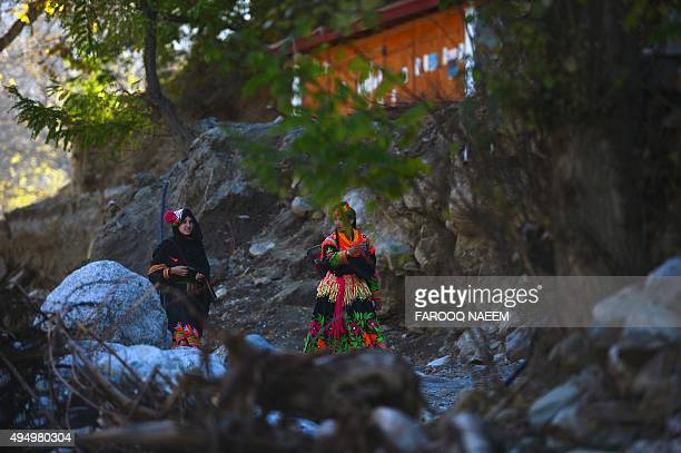 Kalash women walk on a street in Bumburate on October 30 2015 Kalash considered as the only surviving animist tribe of Pakistan was badly affected by...