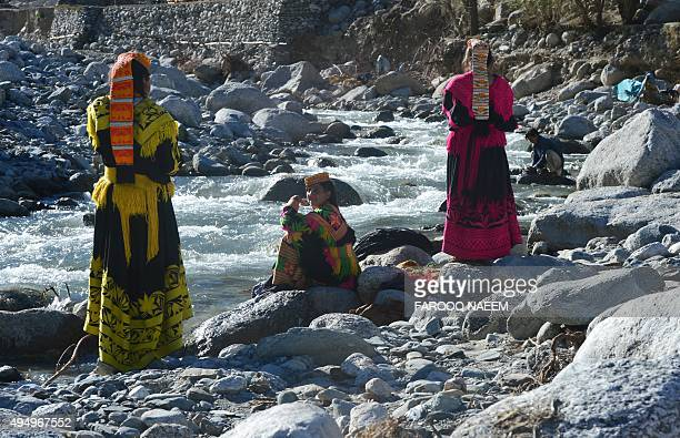 Kalash women wash their clothes in a stream at the Bumburate village of Kalash valley on October 30 2015 The Kalash considered the only surviving...